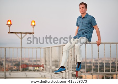 Young man in denim clothes sits on the fencing of the building roof. - stock photo