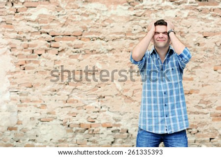young man in despair on brick wall background - stock photo