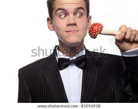 young man in dinner jacket with mushroom making faces - stock photo
