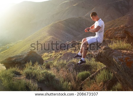Young man in fitness clothing running along mountain  - stock photo