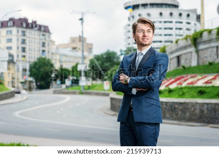 Young man in formal attire is standing beside the road. Businessman with arms crossed and looking away - stock photo