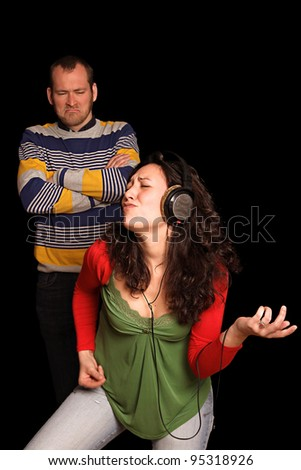 young man in front of black background feels ignored by his girlfriend that is having fun listening to her favourite rock music on her headphones - stock photo