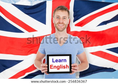 Young Man In Front Of British Flag Holding Digital Tablet With Learn English Text - stock photo