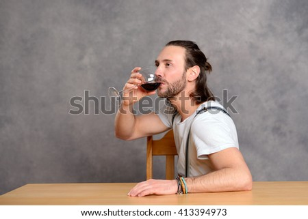 young man in front of gray background drinking red wine - stock photo