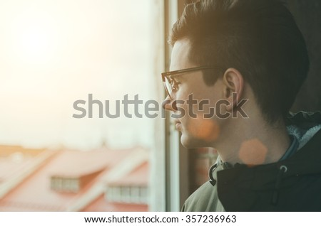 Young man in glasses looking in window - stock photo