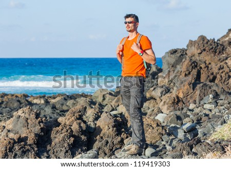 Young man in glasses with backpack. Backround blue sea - stock photo