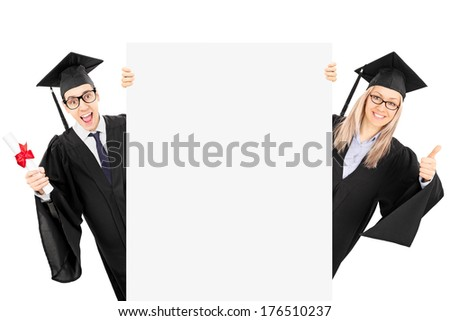 Young man in graduation gown holding diploma and a girl giving thumb up behind blank panel isolated on white background - stock photo