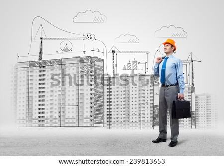 Young man in hardhat and construction sketches at background - stock photo