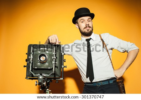 Young man in hat as photographer with retro camera on an orange background - stock photo