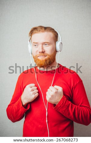 young man in headphones with closed eyes listening to the unpleasant or out of tune music - stock photo