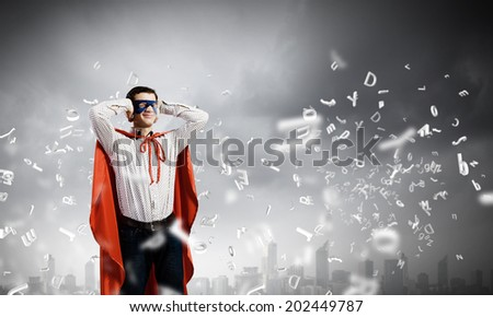 Young man in hero costume closing ears with palms - stock photo