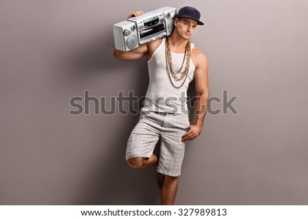 Young man in hip-hop clothes carrying a ghetto blaster over his shoulder and leaning against a gray wall - stock photo