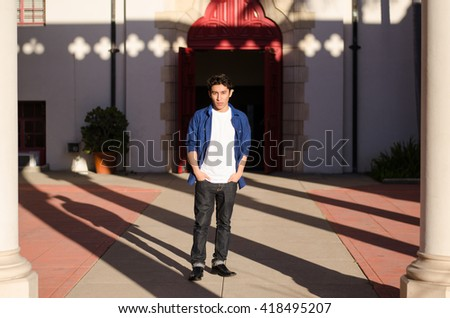 Young man in jeans and shirt standing in a courtyard; shadows, portrait - stock photo