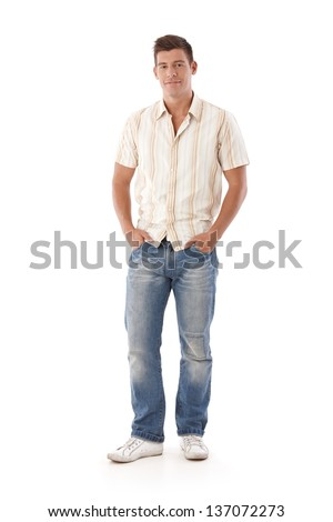 Young man in jeans and shirt standing with hands in pocket. - stock photo