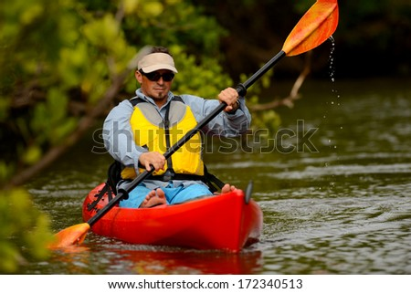 young man in kayak in a tropical location - stock photo