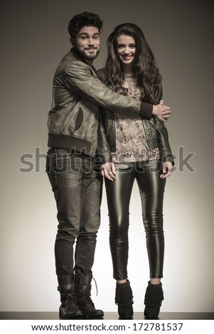 young man in leather jacket embracing his girlfriend in studio - stock photo