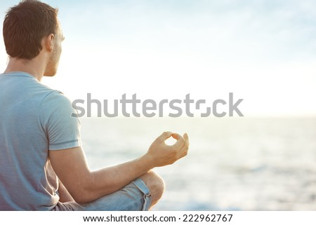 young man in meditation near the sea - stock photo