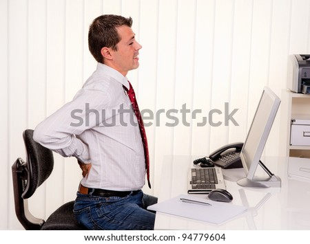 young man in office with computer and back pain - stock photo
