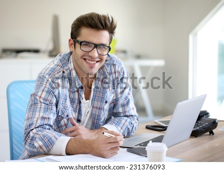 Young man in office working on laptop computer - stock photo