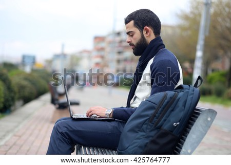 Young man in park with Laptop - stock photo