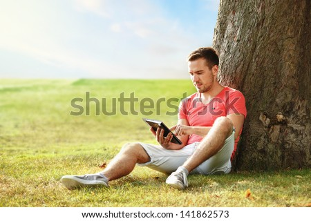 young man in pink t-shirt with tablet in the park - stock photo