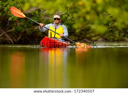 young man in red kayak in tropical destination - stock photo