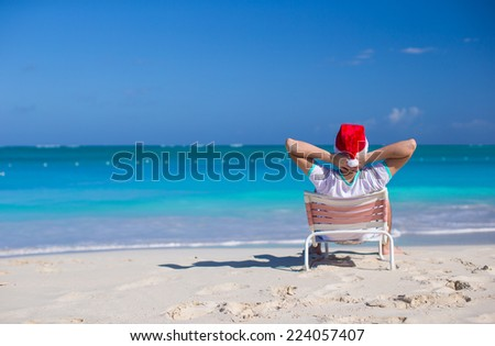 Young man in santa hat during beach vacation - stock photo