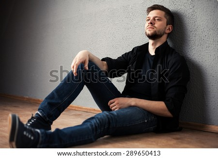 Young man in shirt siting with hands clasped against a wall - stock photo