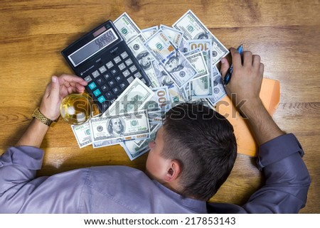 Young man in shirt tired and fell a sleep counting money on a calculator with a pen in hand on a hundred dollar bill at the table - stock photo