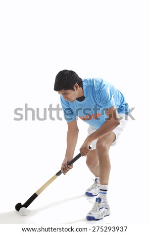 Young man in sportswear playing hockey isolated over white background - stock photo
