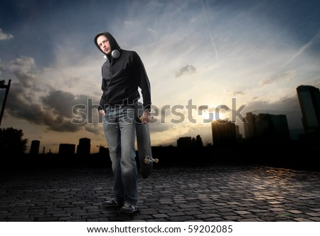 Young man in street-wear standing on a city street - stock photo