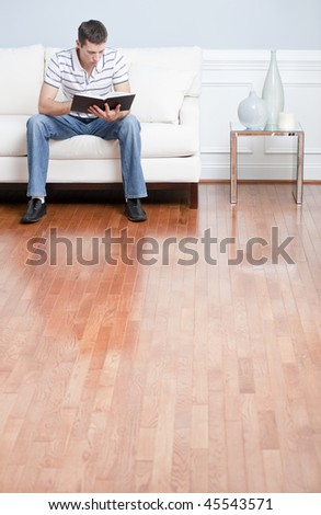 Young man in striped shirt and blue jeans sitting on white sofa reading a book. Vertical shot. - stock photo