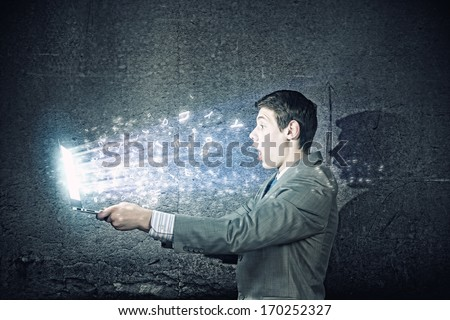 Young man in suit looking astonished in laptop. Surfing the internet - stock photo