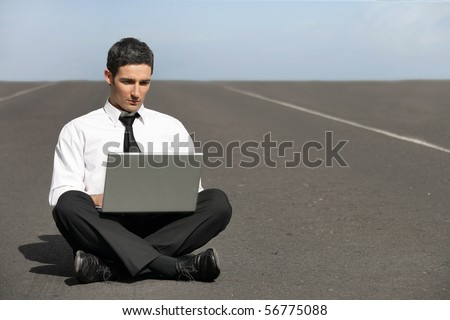 Young man in suit sitting in front of a laptop computer - stock photo