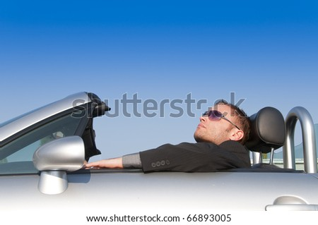 Young man in suit sitting in his open sports car convertible. - stock photo