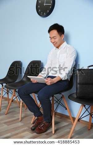 Young man in suit sitting on chair with tablet and waiting for job interview indoors - stock photo