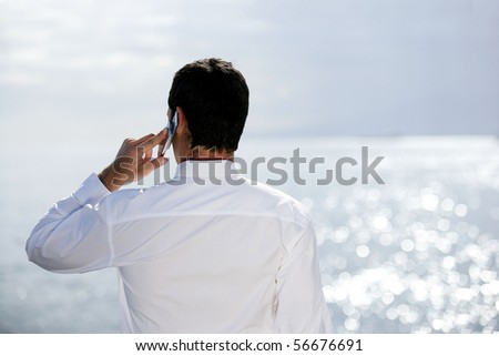 Young man in suit with a phone face to the sea - stock photo