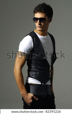 young man in sunglasses against shot in studio - stock photo