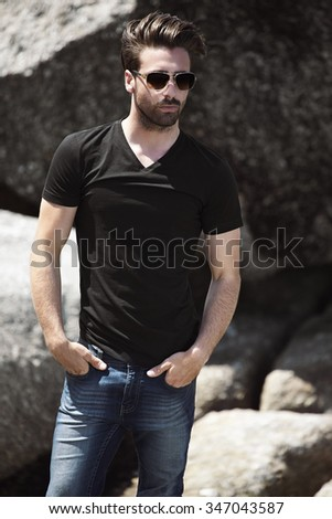 Young man in sunglasses and t-shirt - stock photo