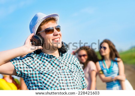 young man in sunglasses, headphones holds a hand on a background of blue sky and friends - stock photo