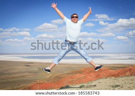Young man in sunglasses jumping over blue sky - stock photo