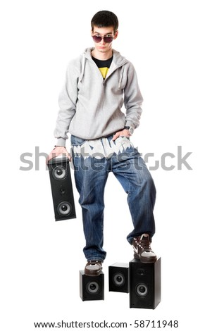 Young man in sunglasses standing on the speakers. Isolated - stock photo