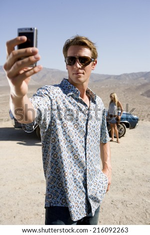 Young man in sunglasses taking photograph by woman and car in desert - stock photo