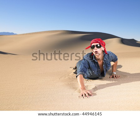Young man in sunglasses wearing red bandana crawling in sand. Horizontal shot. - stock photo