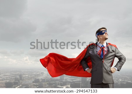 Young man in superhero costume representing power and courage - stock photo