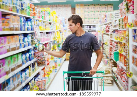 young man in supermarket - stock photo
