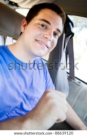 Young man in the car strapping on his seat belt - stock photo