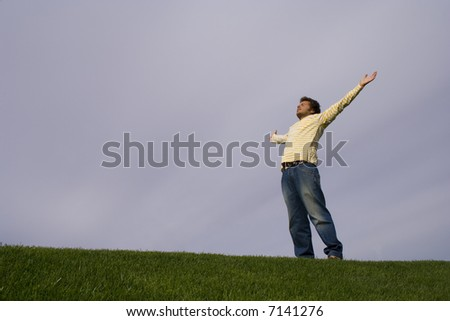 young man in the grass looking to the sky with his arms outstretched - stock photo