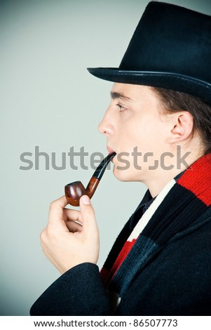 young man in top hat smoking a pipe - stock photo