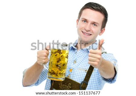 young man in traditional bavarian tracht holds Oktoberfest beer stein and shows thumb up - stock photo